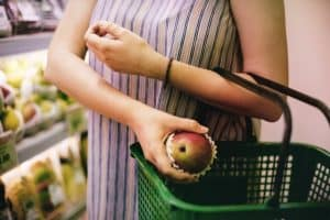 Woman grocery shopping and placing fruit in basket